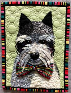 A1-Monica Kaseman – Spiffy Pippin – When I looked at the inspiration photograph, two things stood out:  the dog and the rainbow colors.  So I made a portrait quilt of our dog Pippin sporting a rainbow colored tie.